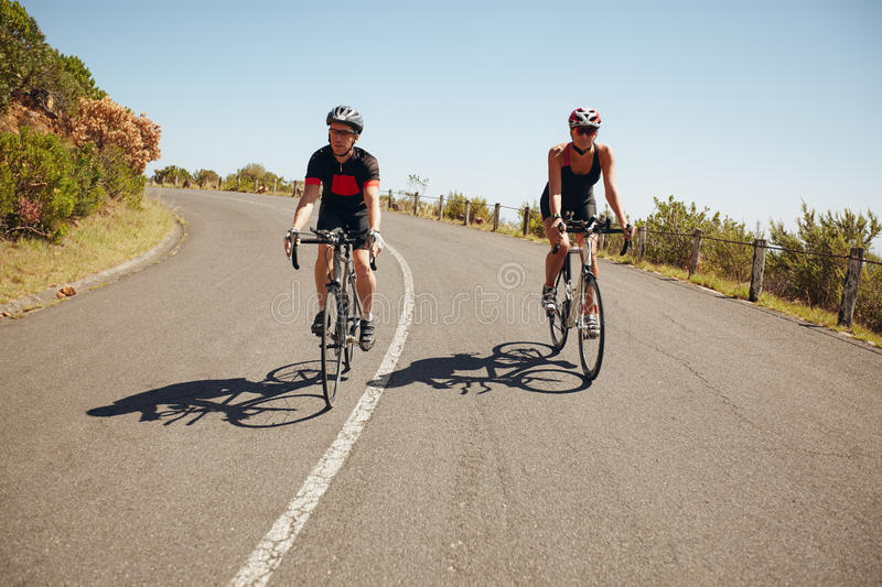 Cyclists riding down a country road stock images