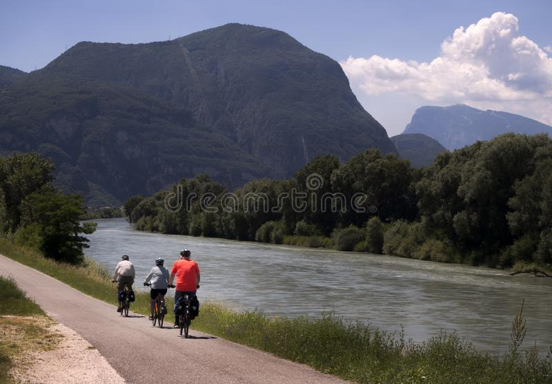 Cyclists on riverside bike way with mountain view. Three cyclists in Italy riding along a river with mountains in the background. It is summer and they are stock photography