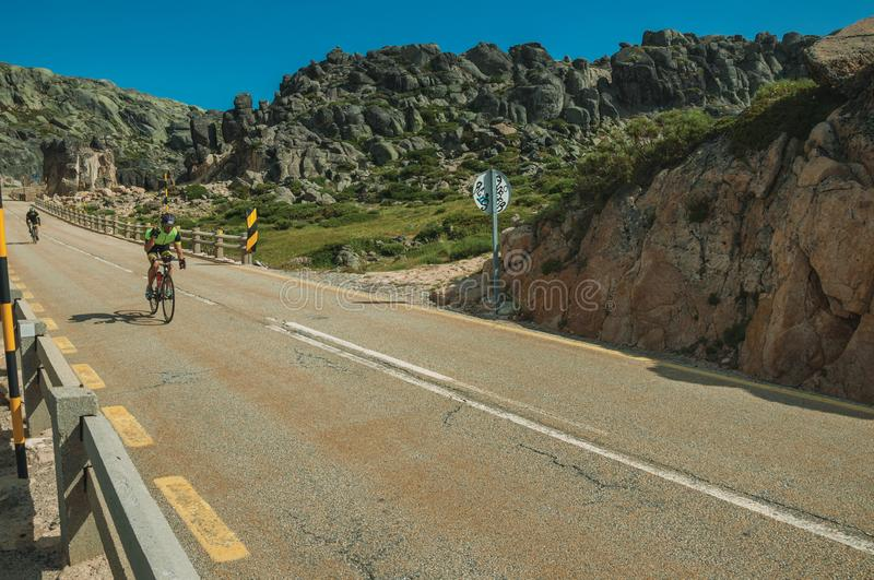 Cyclists on road passing through rocky landscape stock photos