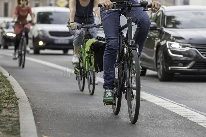 Cycle_lane. Cyclists on street lane beneath cars stock photography