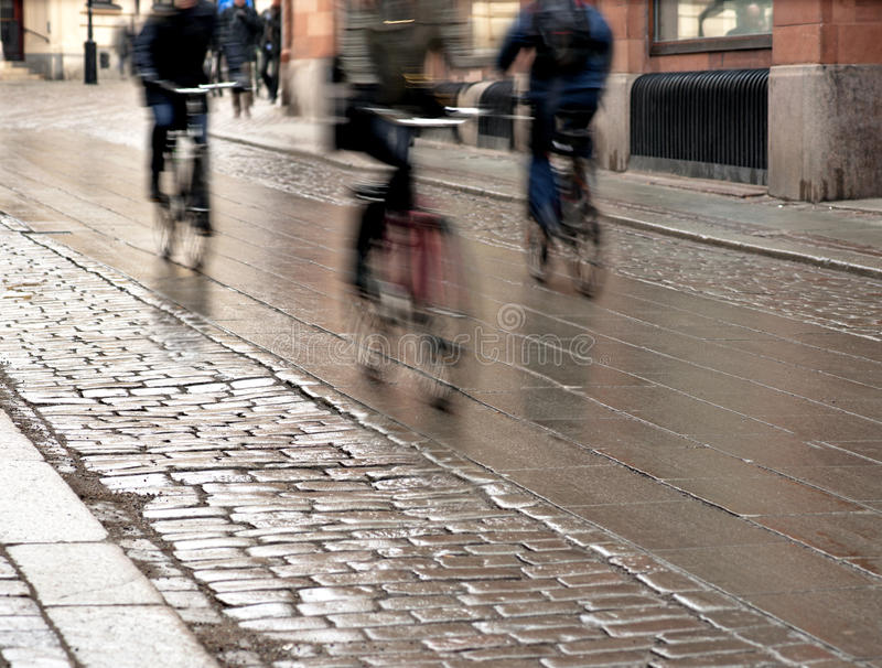 Cyclists on wet street stock images