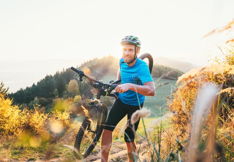 Cyclo-cross competition member Man mountain biker carrying his b. Ike up on hill top royalty free stock image