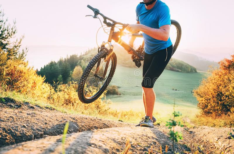 Cyclo-cross competition member Man mountain biker carrying his. Bike up on hill top stock image