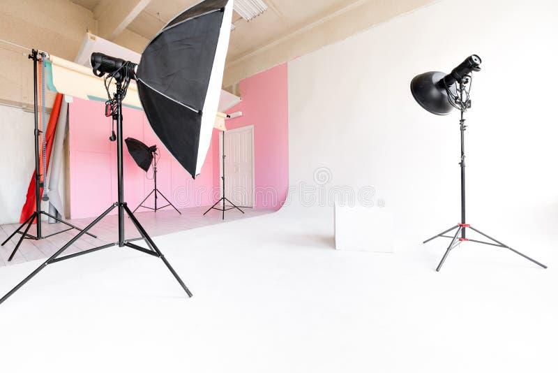 Cyclorama branco do grande espaço do estúdio e luz natural das grandes janelas equipamento e flash de iluminação foto de stock royalty free