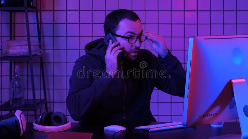 Cyfrowanie specjalista w przypadkowym z komputerem i opowiadać telefonem podczas gdy kodujący informację tworzyć dogodnego oprogr zdjęcie stock