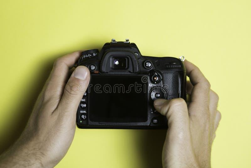 Cyfrowego Pojedynczego obiektywu odruch na żółtym tle, ekranizuje z widoku z góry Ręka dotyka kamerę fotografia royalty free