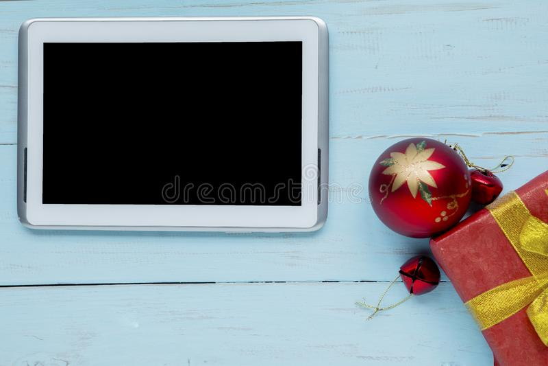 Cyfrowej pastylka z Bożenarodzeniową piłką na stole obrazy stock