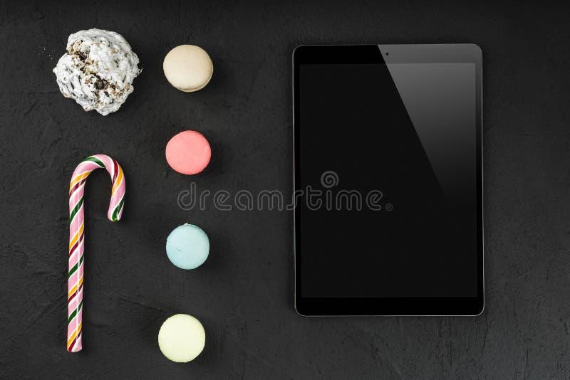 Cyfrowej pastylka z słodkimi macarons, lizakiem i ciastkiem na kamiennym tle, Odbitkowa przestrzeń, mieszkanie nieatutowy fotografia stock
