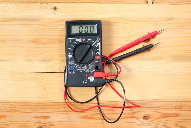 Cyfrowy multimeter i drutowanie na drewnianym stole specjalny elektryczny i technik używa fotografia stock