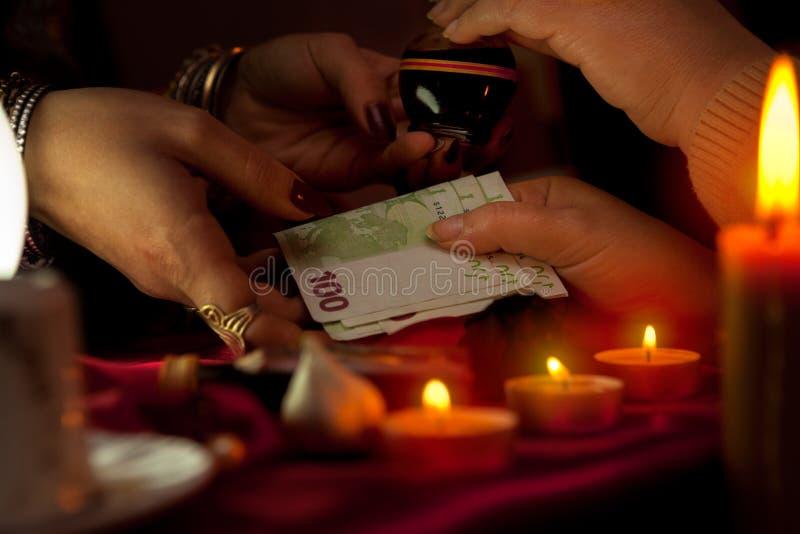 Cygańska kobieta bierze pieniądze od jej klienta dla magicznego napoju miłosnego obrazy royalty free