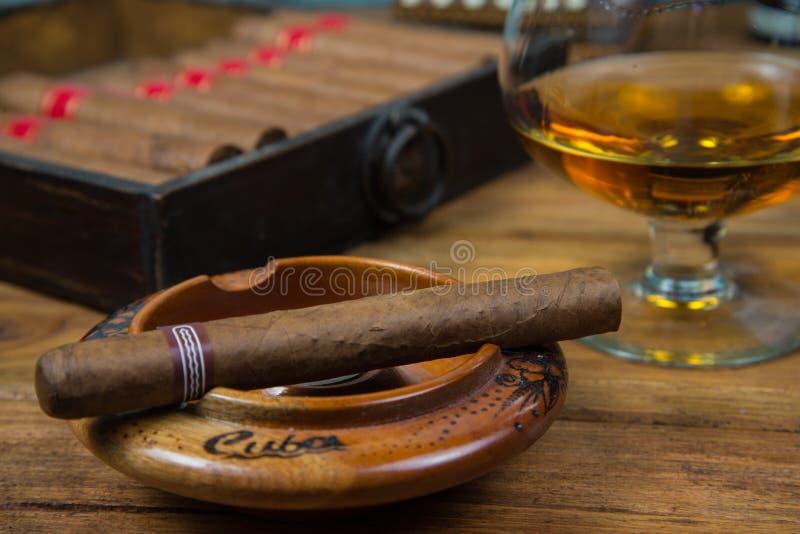 Cygara, rum i alkohol na stole fotografia royalty free