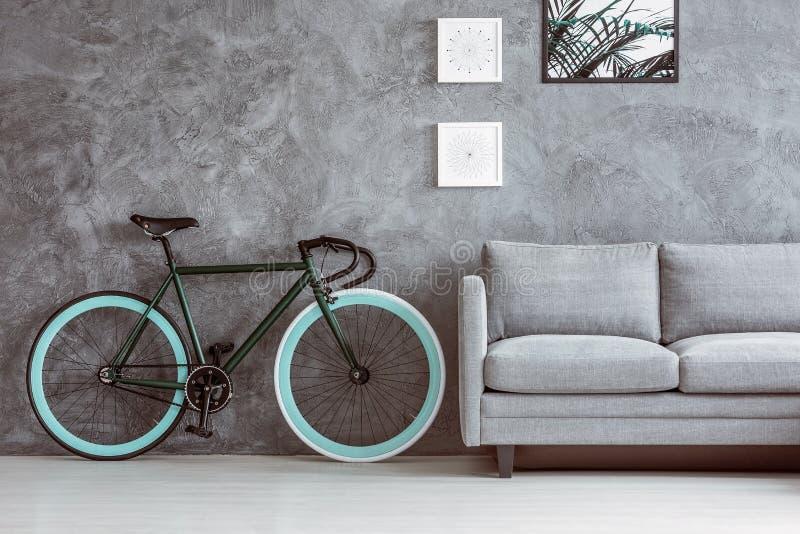 Cykel bredvid den gråa soffan royaltyfri foto