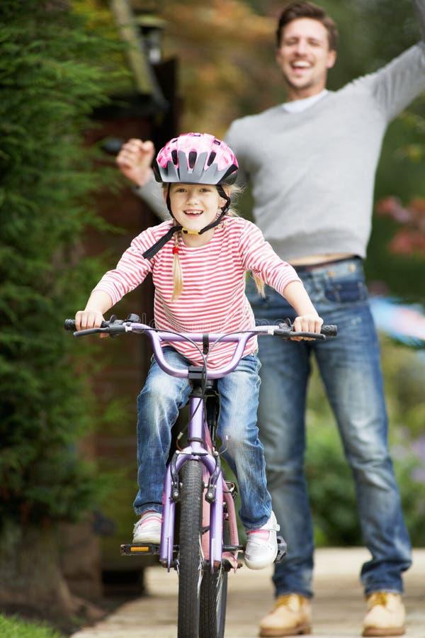 Cykel för faderTeaching Daughter To ritt i trädgård fotografering för bildbyråer