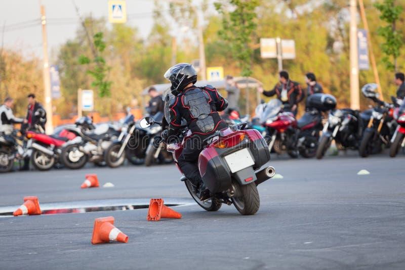 Cykel för mopedchaufförridning på stads- fyrkant genom att använda den som motordrome, bakre sikt royaltyfri fotografi