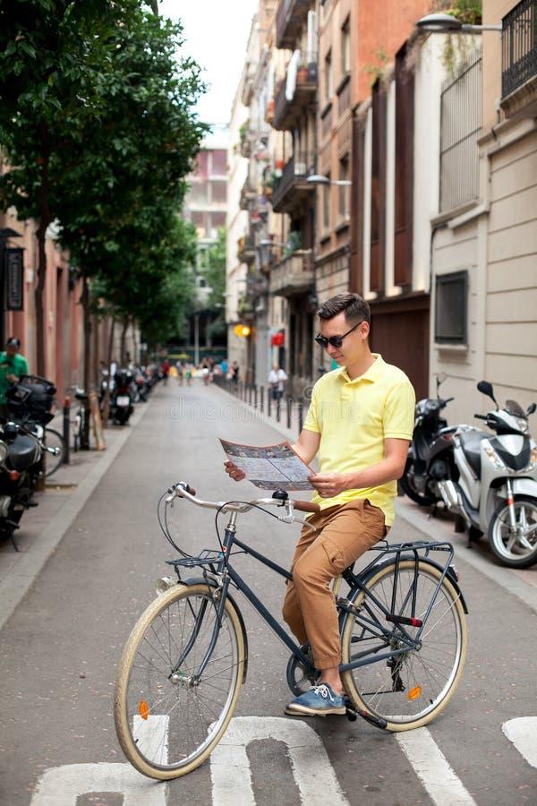 Cykel för tappning för Hipstermanridning och läsningöversikt i turist- område i europeisk stad arkivfoto
