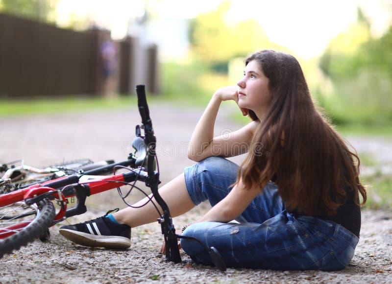 Cykel för tonåringflickaritt på landsvägen till och med skogen royaltyfri bild
