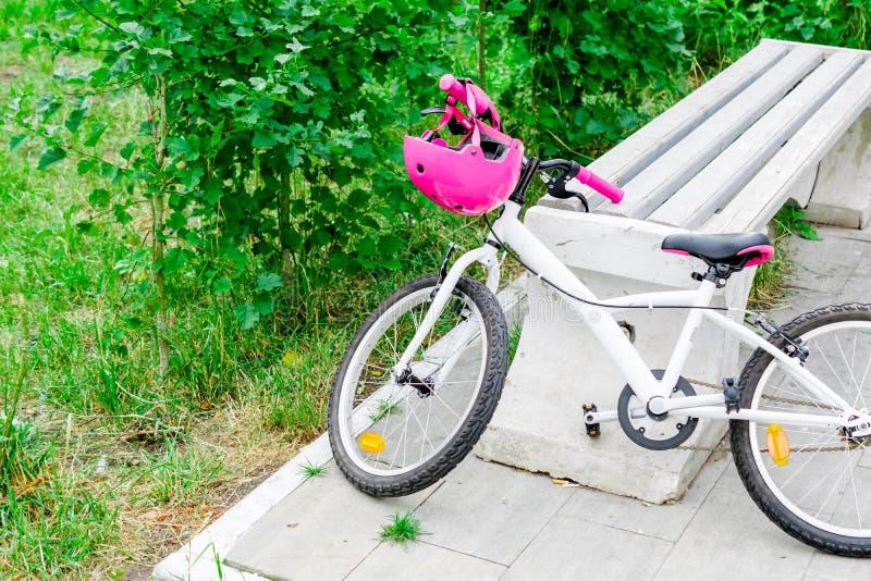 Cykel för tonårs- flicka med den rosa skyddande hjälmen royaltyfri bild