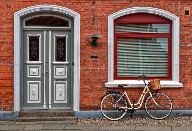 Cykel framme av det röda huset fotografering för bildbyråer