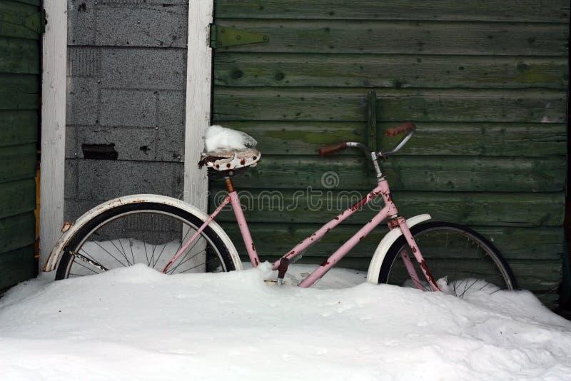 Cykel i snö vid det gamla skjulet royaltyfria foton