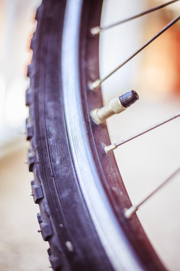 Cykel i staden: N?ra ?vre bild av den d?ckuttaget och eker royaltyfri foto