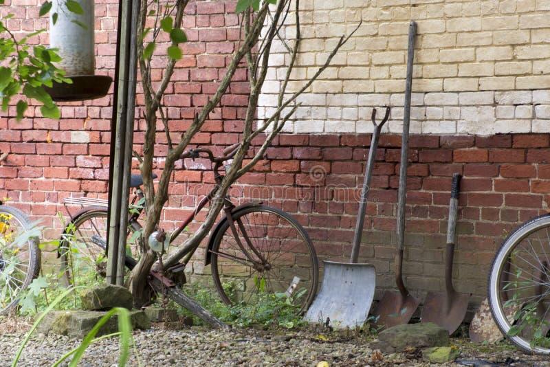 Cykel och skyfflar mot väggen royaltyfri bild