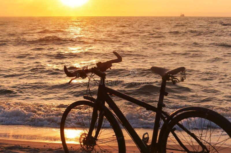 Cykel och solnedgång vid havet, svart cykel vid havet arkivfoton