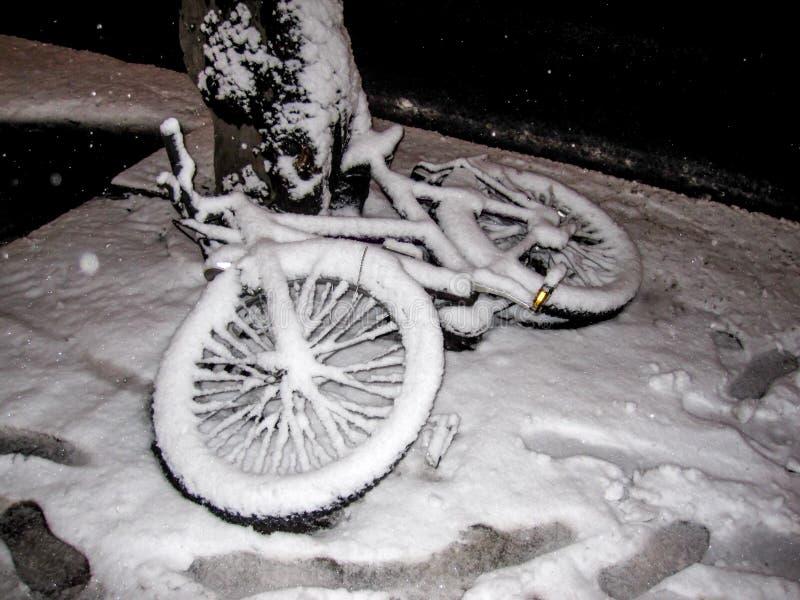 Cykel som överges i gatan och täckas i vit snö efter en vinterstorm i Helsingfors, Finland royaltyfri foto