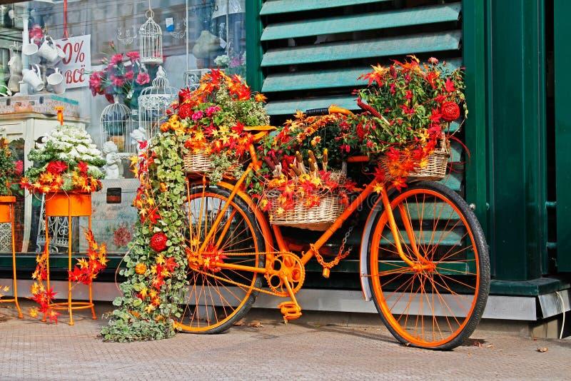 Cykel som dekoreras med höstblommor, sidor, pumpor och havre arkivfoto