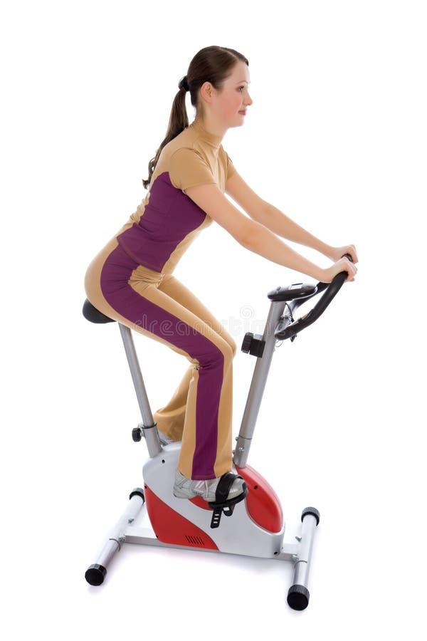 cykel som gör den stationära kvinnan för kondition royaltyfri foto