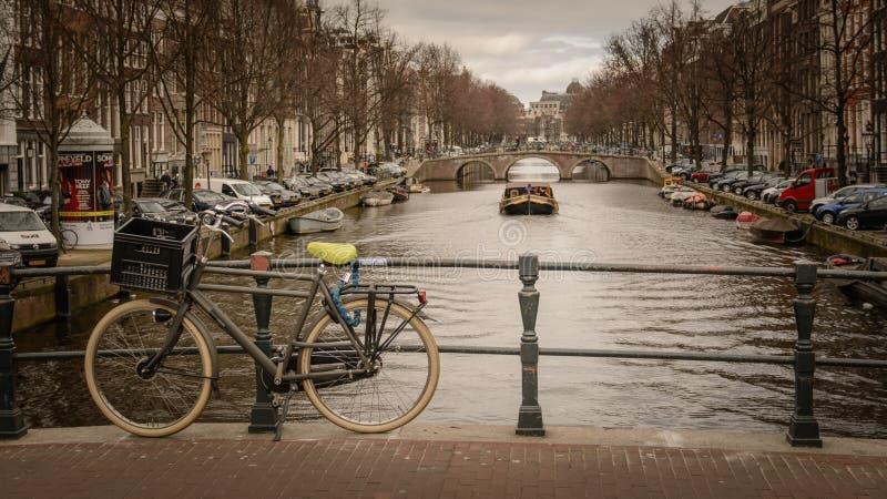 Cykel som låsas på en bro över en kanal i Amsterdam Nederländerna Mars 2015 royaltyfri fotografi