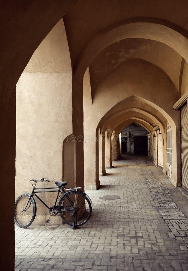 Cykel som parkeras i en traditionell passage med Clay Arches i stad av Yazd royaltyfri foto