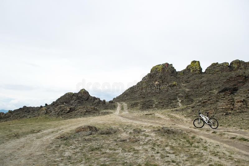 Cykelanseende på en väg bland klippan royaltyfri bild
