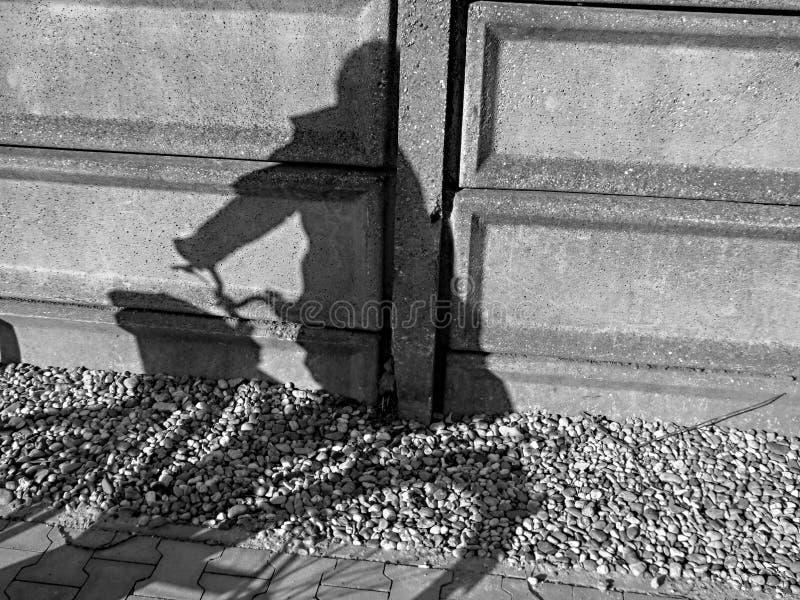 Cykelcykelskugga på stenväggen med folk fotografering för bildbyråer