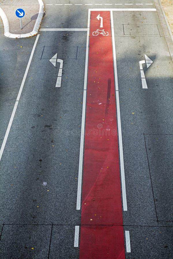 Cykelgränd med rött markerings- och cykelsymbol på asfalten roa royaltyfri fotografi