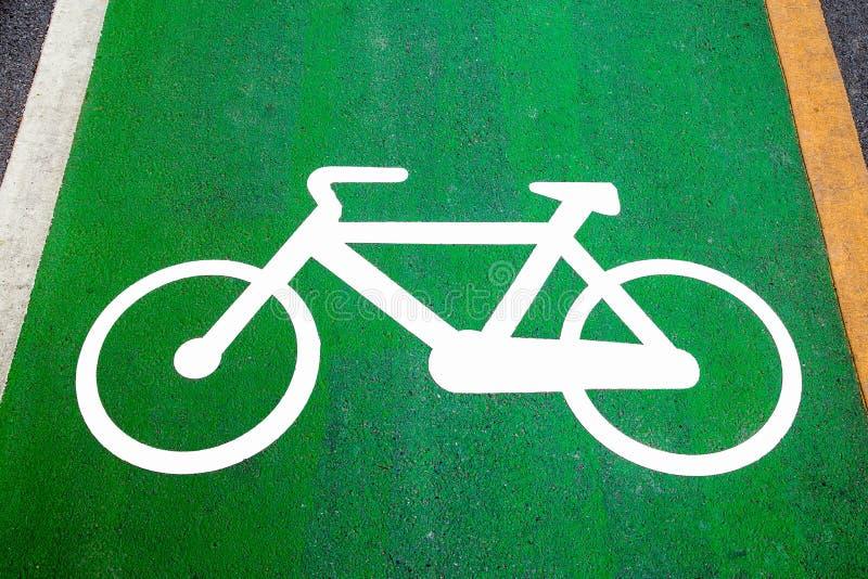 Cykelgrändtecken som målas på en grön cykelgränd (cykelgränden, väg royaltyfria bilder