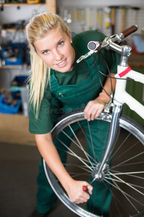 Cykelmekaniker som reparerar hjulet på cykeln i ett seminarium arkivbilder