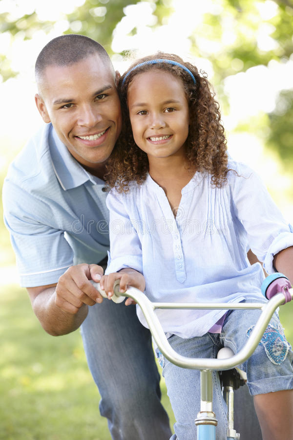 Cykeln för den faderTeaching Daughter To ritten parkerar in royaltyfria foton