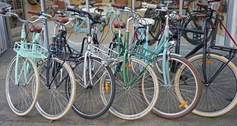 Cykeln för den tappningLekker shoppar den cyklar parkerade utmärkt i rad yttersidan fotografering för bildbyråer