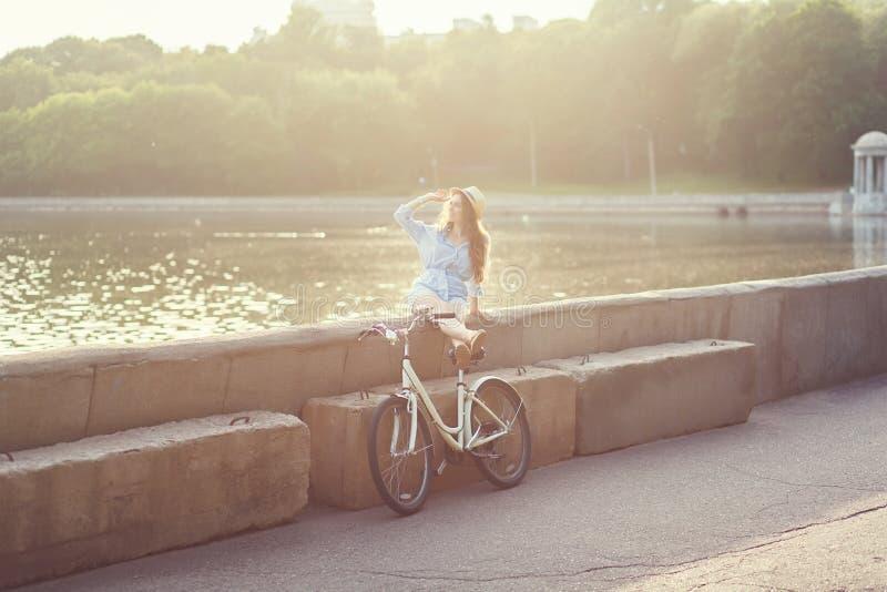 Cykeln för kvinnaridningtappning parkerar på royaltyfri fotografi