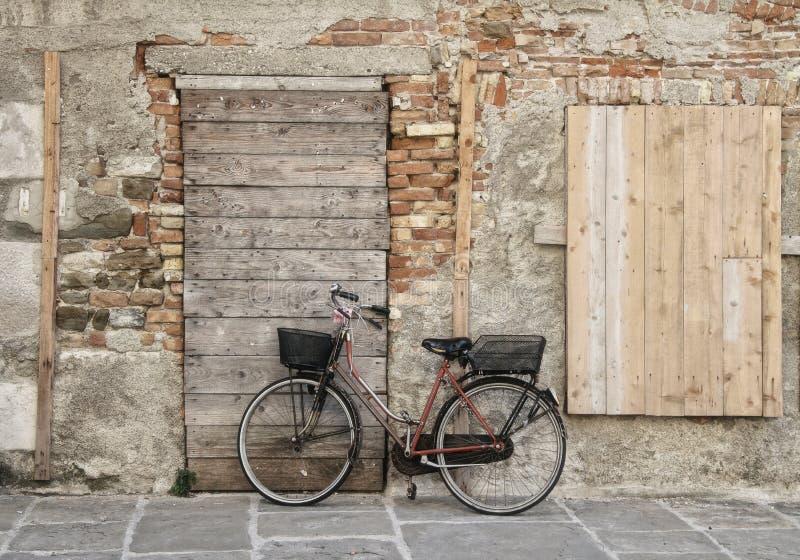 Cykeln st?r p? de pittoreska v?ggarna av det gamla huset royaltyfri foto