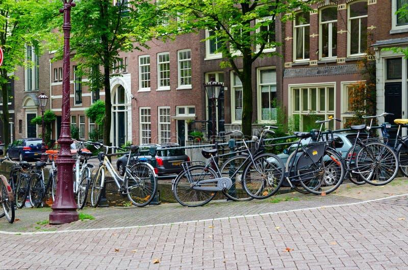 Cykelparkering på gatan i historisk mitt av Amsterdam, Nederländerna arkivfoto