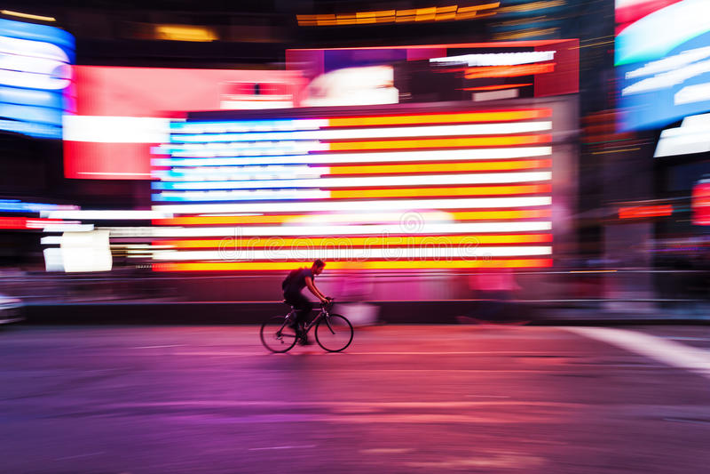 Cykelryttare framme av fyrkanten för USA-flagga tidvis, NYC, i rörelsesuddighet royaltyfri fotografi