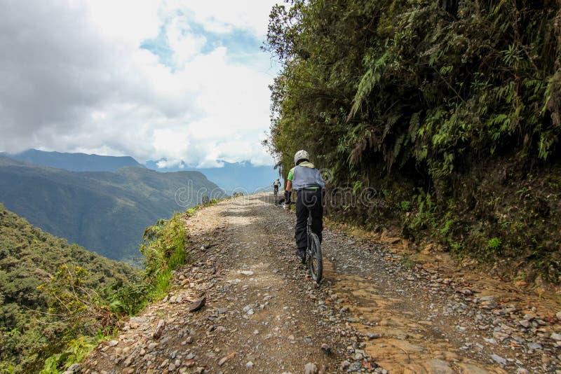 Cykelryttare på den Camino de la muerte/Yungas vägen arkivfoto