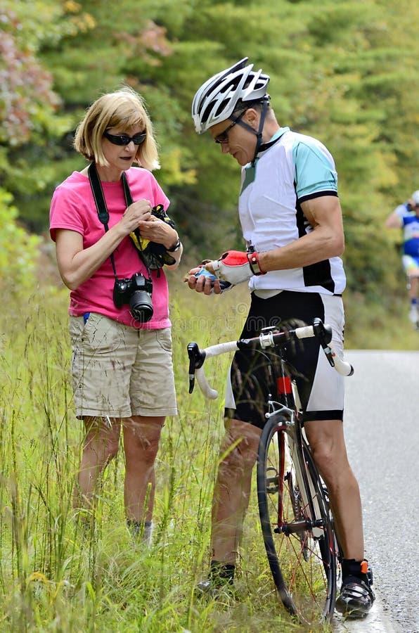Cykelryttare som får hjälp royaltyfria foton