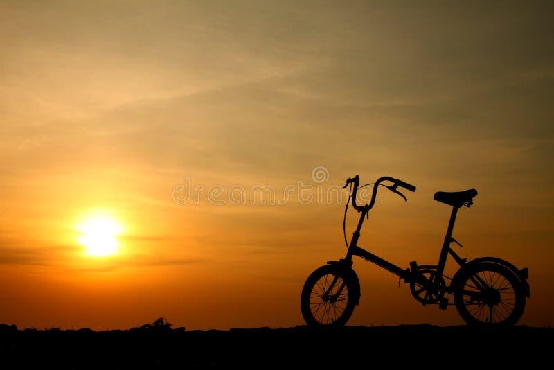 cykelsilhouettesolnedgång royaltyfri foto
