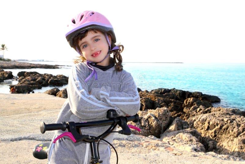 cykla den lyckliga hjälmen för flickan little rosa stenigt hav royaltyfri foto