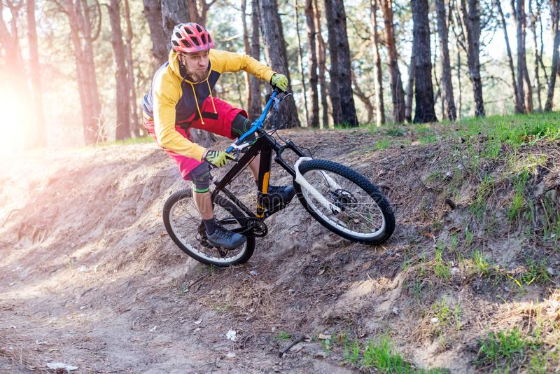 Cykla en cyklist i ljus kläder som rider en mountainbike till och med träna aktiv livsstil royaltyfri fotografi