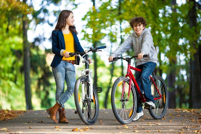 Cykla för tonårs- flicka och för pojke arkivfoton