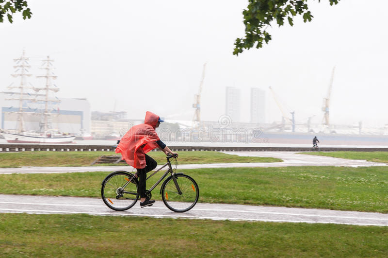 Cykla i regn royaltyfri foto