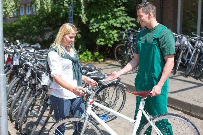 Cykla mekanikern som visar en ny cykel till kunden arkivfoto